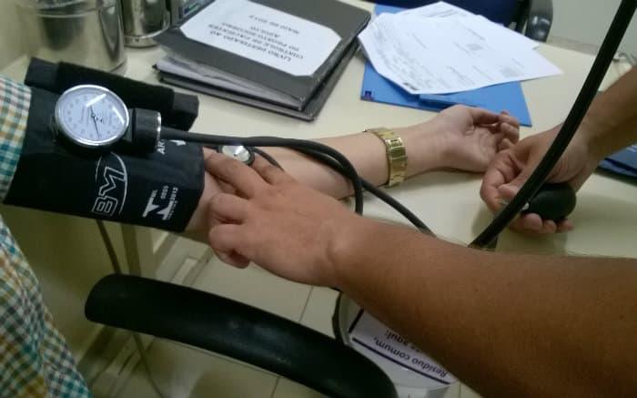 Imagem de médico medindo a pressão de paciente para texto sobre AMA