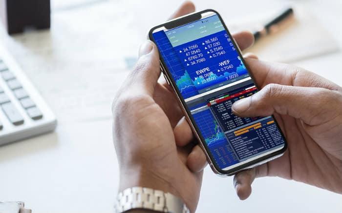 Imagem de empresário com celular na mão para ilustrar texto sobre aplicativos para finança de empresa