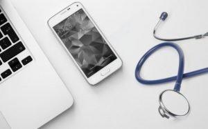 Imagem de computador, celular e estetoscópio para ilustrar texto sobre plano de saúde por categoria profissional.