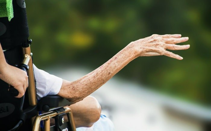 Imagem de idoso em cadeira de rodas para ilustrar texto sobre cuidados paliativos na medicina