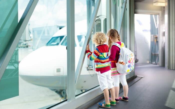Imagem de duas crianças no aeroporto para ilustrar texto sobre viajar nas férias de julho