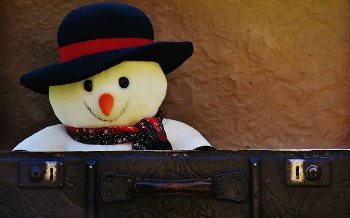 Imagem de boneco de neve e uma mala para ilustrar texto sobre mala de inverno
