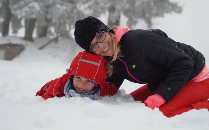imagem de mulher e criança na neve para texto sobre viajar no inverno