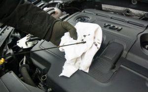 Imagem de pessoa trocando o óleo para texto sobre quando trocar o óleo do carro