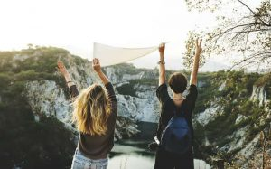 Imagem de duas mulheres viajando para texto que fala se viajar sem seguro viagem vale a pena ou não.