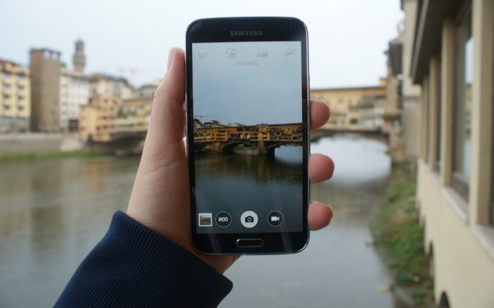Imagem de pessoa titando foto com celular a Itália para ilustrar texto sobre como escolher o melhor seguro viagem para Europa