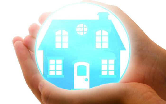 desenho de casa sendo protegida por uma mão para ilustrar texto sobre como acionar seguro residencial