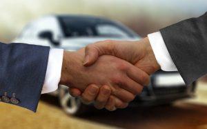 Imagem de aperto de mãos fechando um negócio para texto sobre valor de transferência de veículo
