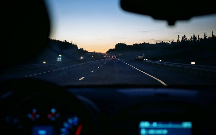 Foto de carro em estrada para texto sobre seguro viagem para aluguel de carro
