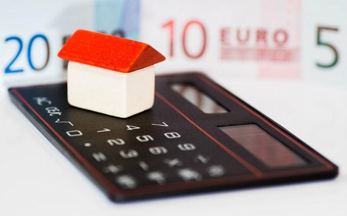 Foto de calculadora e imagem de uma casa para ilustrar texto sobre quem paga seguro residencial.