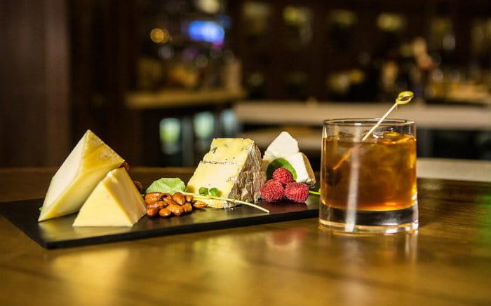 Imagem de queijos e bebida para ilustrar texto sobre o turismo gastronômico