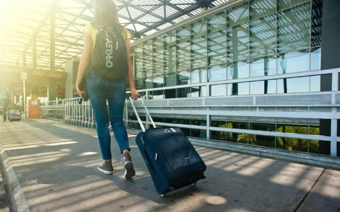 Imagem de pessoa saindo do aeroporto para texto sobre serviço de shuttle
