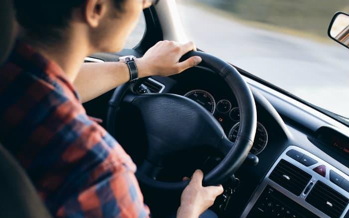 Imagem de pessoa dirigindo para texto sobre seguro por comportamento