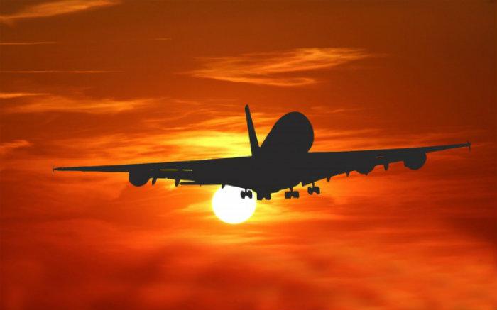 Imagem de avião no ar para texto sobre viagem de fim de ano