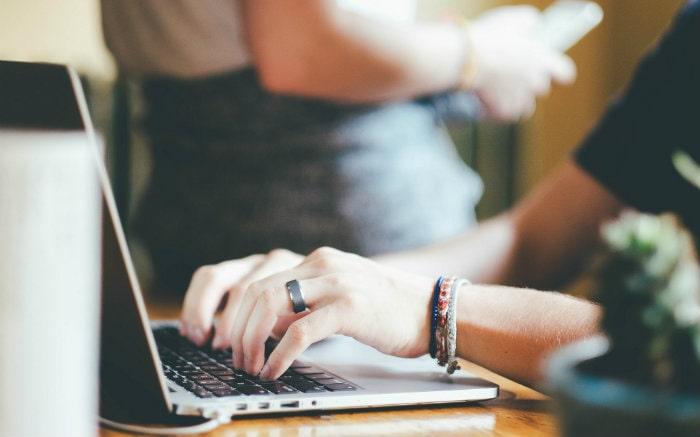 Imagem de pessoa no computador para texto sobre agendamento de consultas online