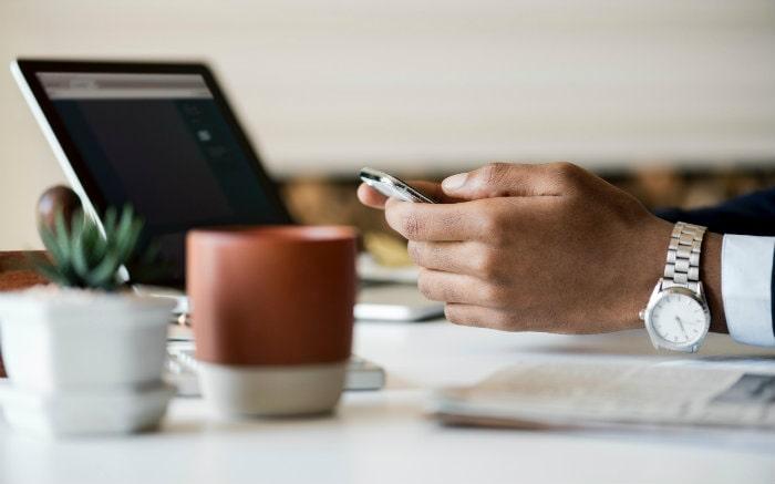 Imagem de pessoa com celular e computador para texto sobre requisitos para empréstimo empresarial