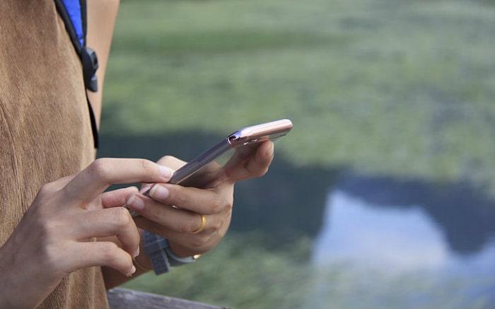 imagem de pessoa com celular para texto sobre aplicativos para viagem