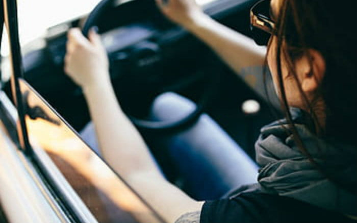 Imagem de mulher dirigindo para texto sobre acessórios para carros femininos