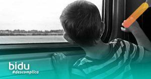 imagem de criança na janela para texto sobre seguro viagem para crianças
