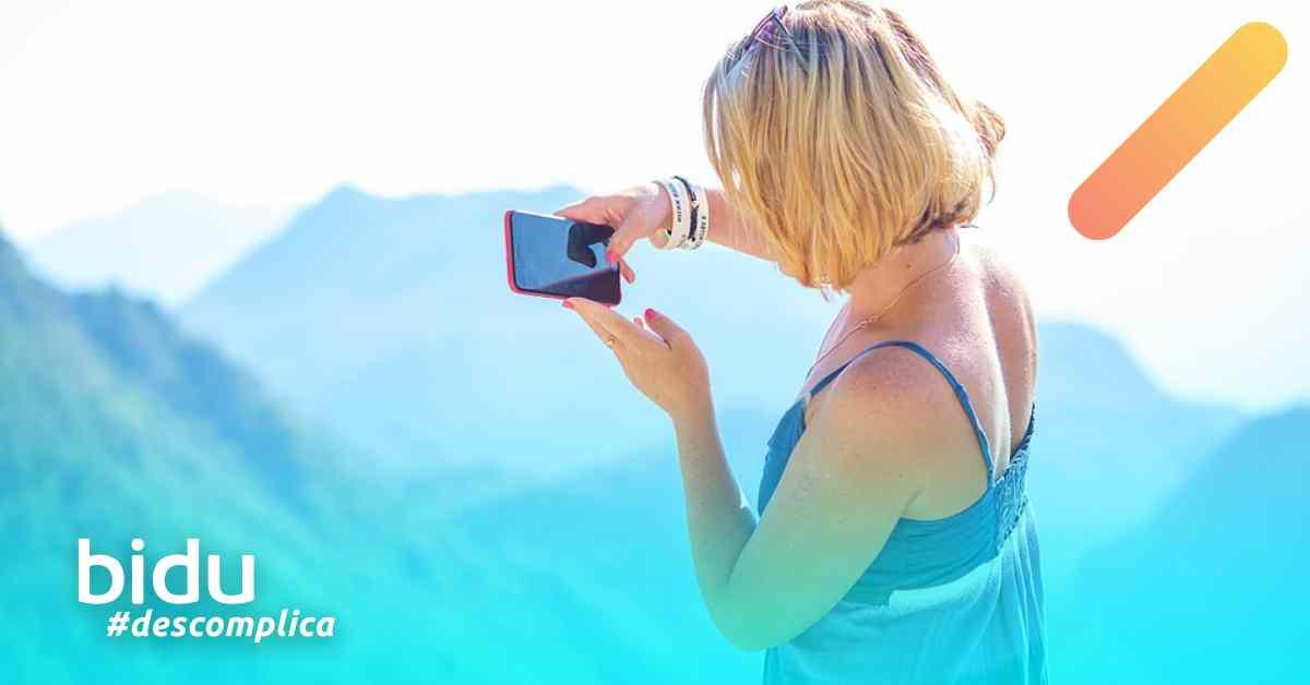 imagem de mulher tirando foto para texto sobre fazer foto sozinho em viagem