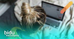 Imagem de mulher no computador para texto sobre como contratar seguro de vida online